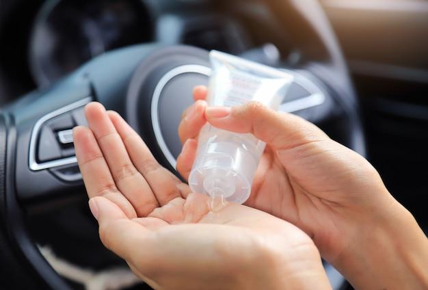 Handpumpen von alkoholgel zum reinigen des lenkrads, bevor das auto tagsüber benutzt wird, um dem vocid- oder corona-virus zu entkommen. menschen kümmern sich um das leben nach dem corona-virus-konzept.