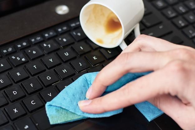 Handreinigung verschütteten kaffee auf laptop-tastatur