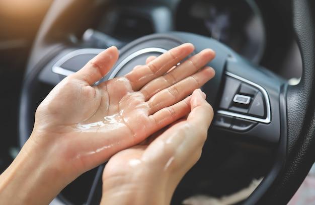 Handreinigungsfinger zur zerstörung von bakterien und viren im auto des lenkrads. menschen, die das leben mit dem konzept des secape corona-virus leben