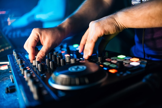Hands dj music mixer regelt die lautstärke