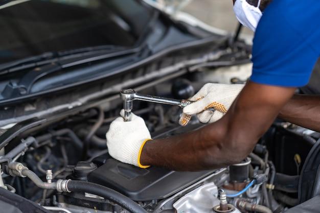 Hands expertise automechaniker im autoreparaturservice. autowartung und autoservice-garage-konzept. schwarzer mann mit medizinischer gesichtsmaske protec virus corona