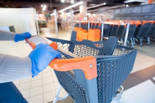 Hands in glives mit einem einkaufswagen in einem supermarkt.