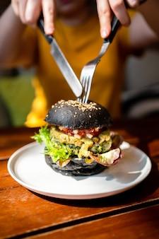 Hands schneidet brokkoli-quinoa-holzkohle-burger mit guacamole, mango-salsa und frischem salat mit messer und gabel, serviert in einem weißen teller. kreatives veganes essen für vegetarier.