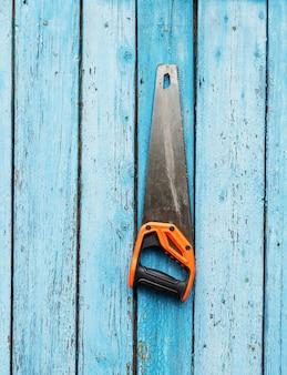 Handsäge hängt an einem nagel an einer blauen holzwand