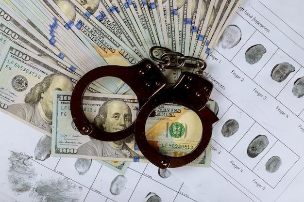 Handschellen auf hundert amerikanischen dollarbanknoten die korruption in der kriminellen fingerabdruckkarte