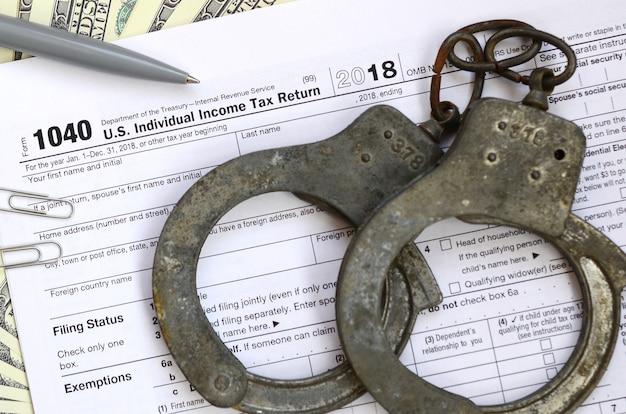 Handschellen der polizei liegen auf dem steuerformular 1040.