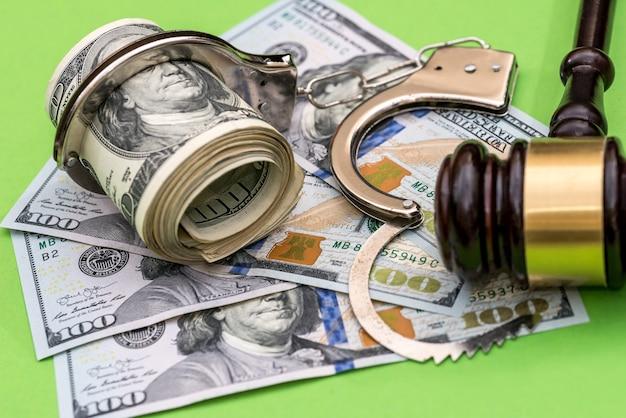 Handschellen, dollarnoten und richterhammer auf grünem hintergrund