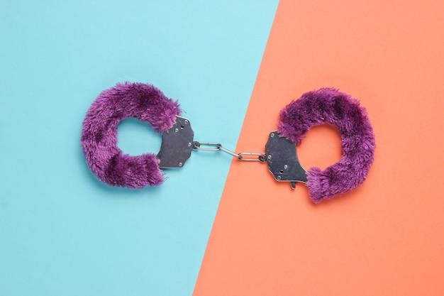 Handschellen für sexspiele auf farbigem hintergrund. sexuelles bdsm-spielzeug. liebeskonzept.