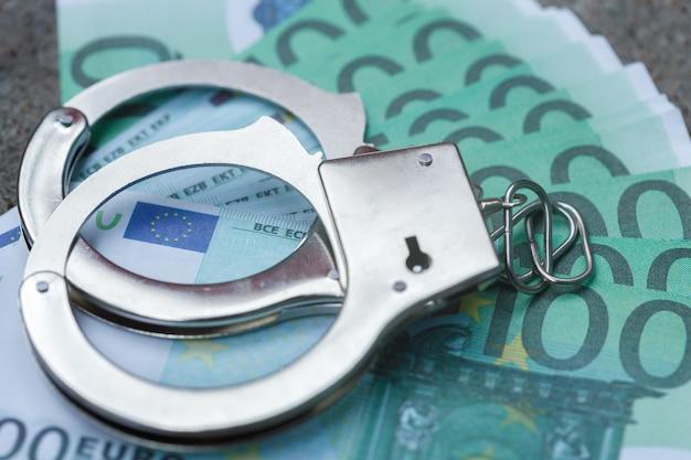 Handschellen liegen auf einer packung mit hundert euro. foto in hoher qualität