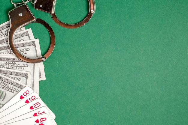 Handschellen liegen neben spielkarten und us-dollar auf einem grünen hintergrund