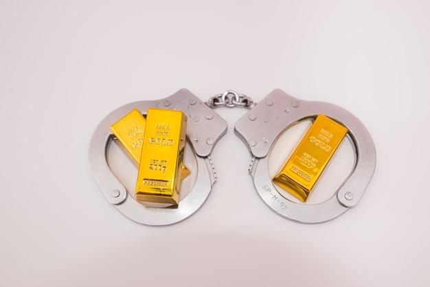 Handschellen und drei goldbarren auf weißem hintergrund.