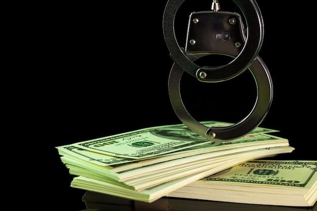 Handschellen wurden an einer dollarbanknote im dunklen hintergrund aufgehängt.