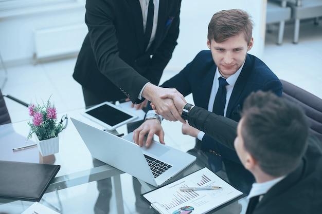 Handschlag des managers und des kunden über dem schreibtisch im büro der bank.