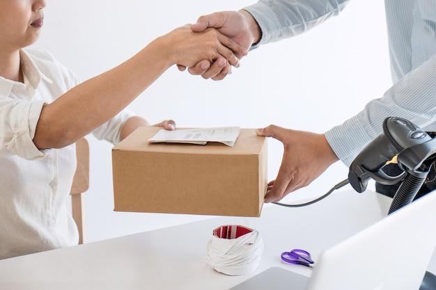 Handschlag des unternehmers kmu, um den auftragskunden zu empfangen und mit der verpackung zu arbeiten