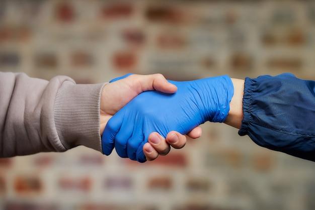Handschlag. eine frau, die einem mann in einem medizinischen einweghandschuh die hand schüttelt, um die ausbreitung des coronavirus (covid-19) zu vermeiden. zwei menschen treffen sich in einer straße.