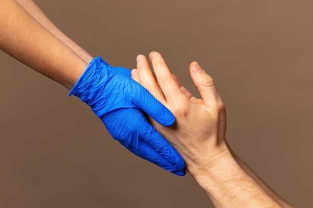 Handschlag in blauen handschuhen, hilfekonzept. persönliche hygiene während einer pandemie