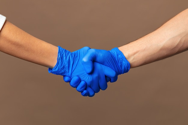 Handschlag in blauen handschuhen, hilfekonzept.