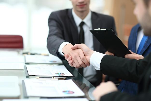 Handschlag von finanzpartnern am schreibtisch.