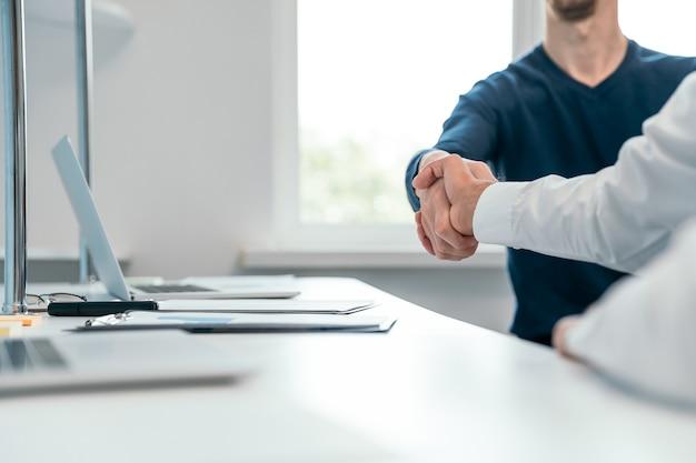 Handschlag von finanzpartnern in der nähe des desktops.