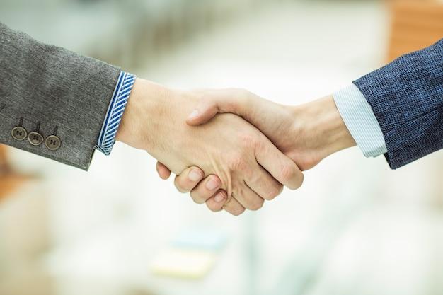Handschlag von geschäftspartnern auf unscharfem hellem hintergrund.