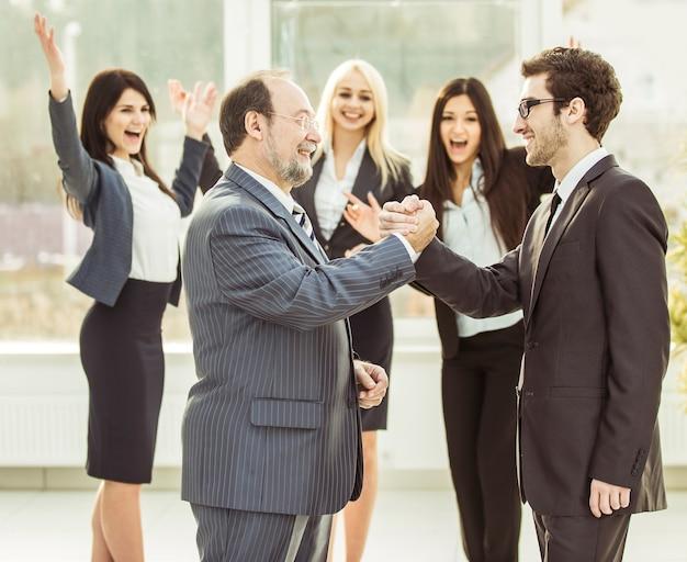 Handschlag von geschäftspartnern vor dem hintergrund des jubelnden geschäftsteams.