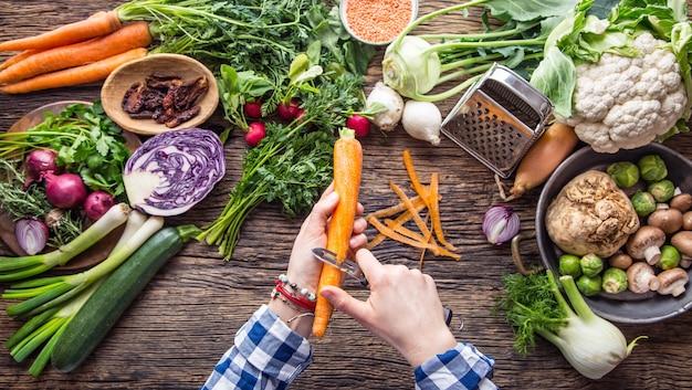 Handschneiden von gemüse. frauenhände schneiden karotten auf holzbrett in der nähe von gemüse.