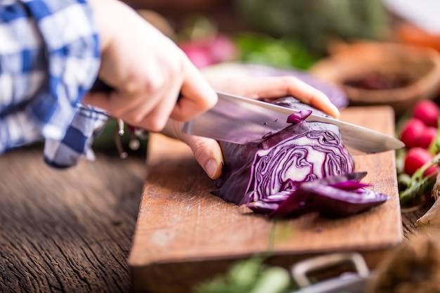 Handschneiden von gemüse. frauenhände schneiden kohl auf holzbrett in der nähe von gemüse.