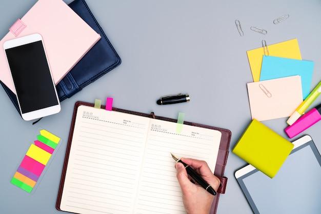 Handschrift auf dem notizbuch umgeben mit bürozubehör.