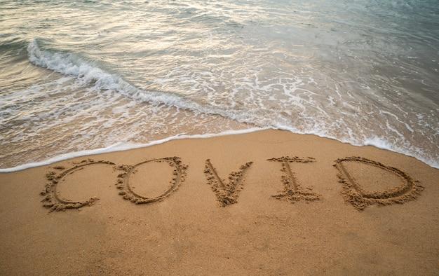 Handschrift covid auf sand und schaumwelle am strand. coronavirus-konzept.