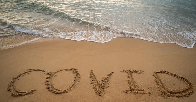 Handschrift covid auf sand und schaumwelle am strand