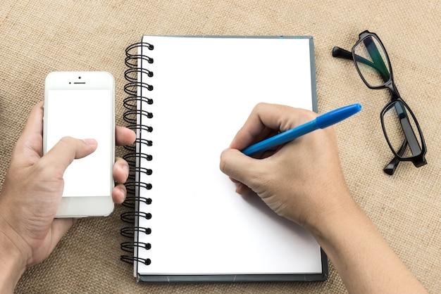 Handschrift des jungen mannes auf leerem notizbuch, während eine andere hand smartphone auf hölzernem vorsprung hält