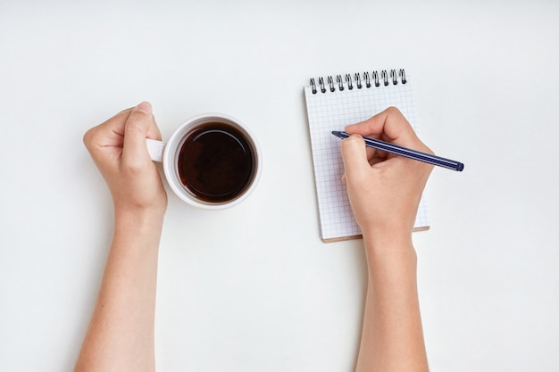 Handschrift. frau schreibt in notizbuch mit stift, genießt guten morgen und heißen tee. schreibkonzept. frau schreibt tagesplan ins tagebuch