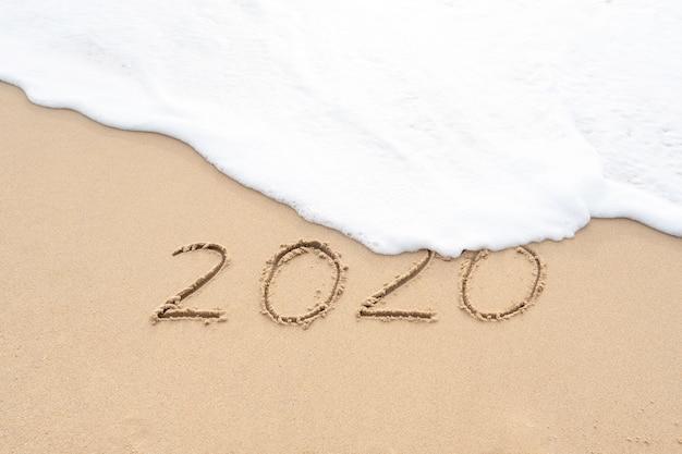 Handschriftliche nummer auf schönem sandstrand auf wiedersehen altes jahr konzept