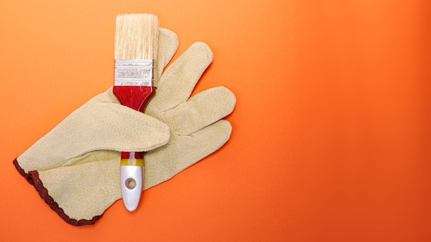 Handschuh, in den der pinsel eingespannt ist. oberflächenmalerei. schutzmittel. heller orangefarbener verlaufshintergrund. kopieren sie platz für text.