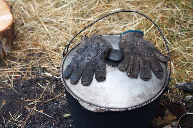 Handschuhe aus ruß liegen auf dem deckel eines topfes mit fertiggerichten in der nähe des feuers