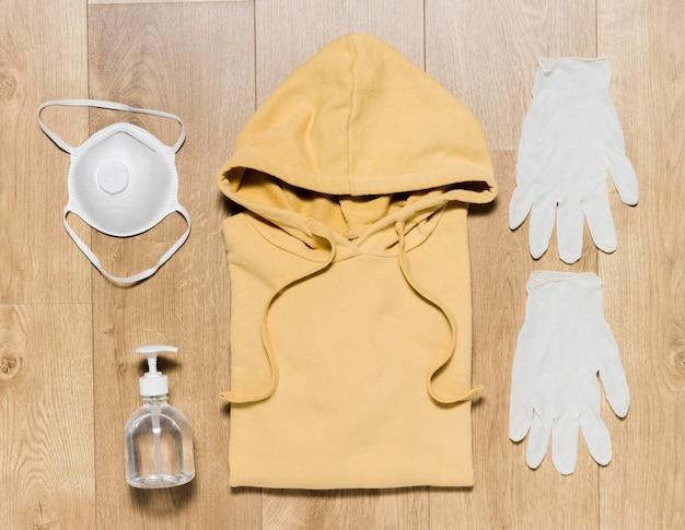 Handschuhe und desinfektionsmittel neben hoodie