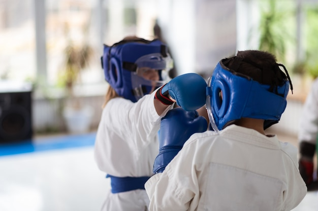 Handschuhe und helme. mädchen und junge, die kämpfen, während sie schutzhandschuhe und helme tragen und kampfkünste üben