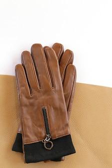 Handschuhe und stücke des echten leders der ledernen frauen lokalisiert auf weißem hintergrund