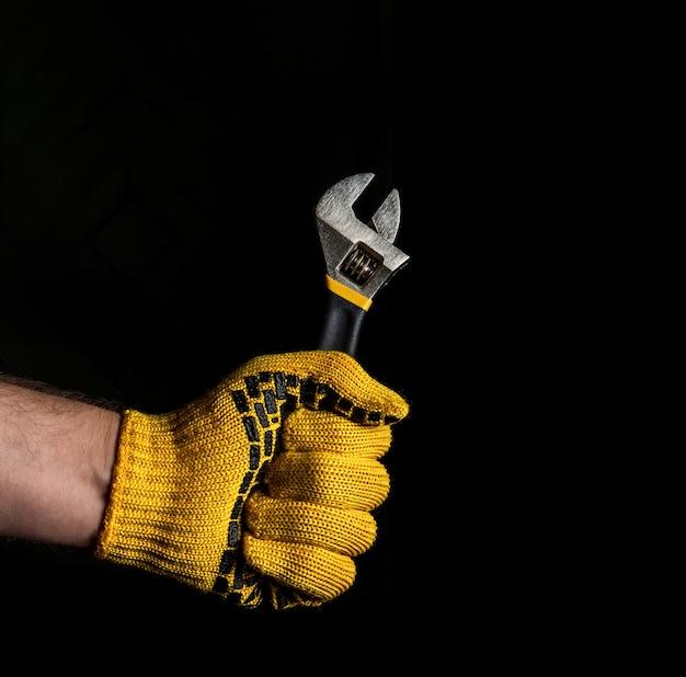 Handschuhhand hält verstellbaren schraubenschlüssel lokalisiert auf schwarzem hintergrund