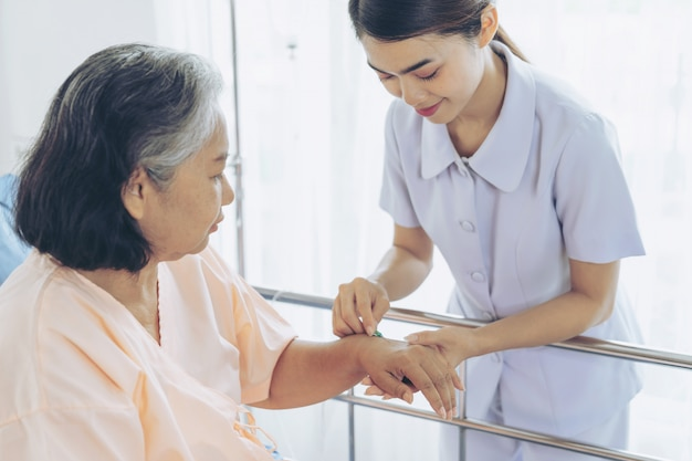 Handschwester hält pille zum injizieren an ältere weibliche patienten, die mit lächelndem, kopierendem raum, gesundem und medizinischem konzept auf bett liegen