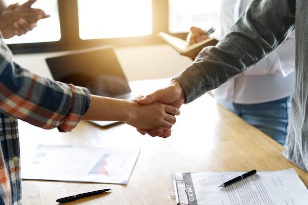 Handshake des stehenden arbeitsteams zwischen mann und frau über der tabelle.