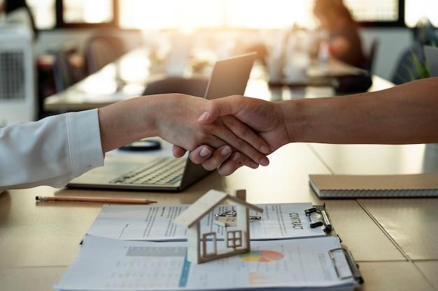 Handshake eine erfolgreiche immobilientransaktion geschäftsleute geben sich die hand, nachdem sie ein haus unterschrieben haben