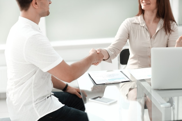 Handshake-geschäftsleute, die am schreibtisch sitzen