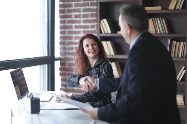 Handshake manager und kunde sitzen an ihrem schreibtisch im büro