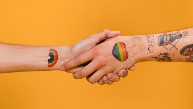 Handshake von paaren von mannhänden mit mehrfarbigem muster des homosexuellen stolzes
