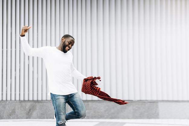 Handsome afroamerikanischen mann mit lässigen kleidung springen und tanzen mit grunge betonwand hintergrund.