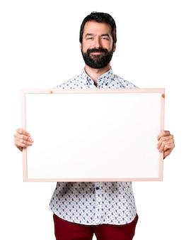 Handsome brunette mann mit bart mit einem leeren plakat
