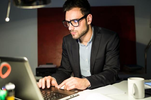 Handsome junge geschäftsmann arbeitet mit laptop im büro.