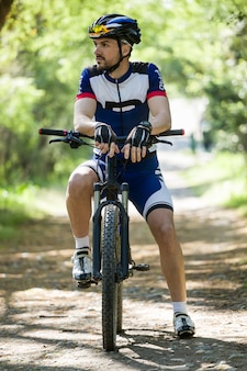 Handsome junge mann entspannenden nach dem radfahren in den bergen.