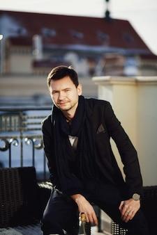 Handsome junge mann sitzt auf dem stuhl im freien